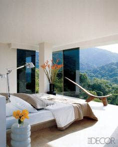In architect Fernando Arriaga's guest room, a concrete bed, an African chair, and a floor of sandblasted marble make the space both minimal and eclectic—but the real drama comes from the wall of glass overlooking Venezuela's lush flora.  Read more: Rooms with Beautiful Views - ELLE DECOR  Follow us: @ELLE DECOR on Twitter | ELLEDECORmag on Facebook  Visit us at ELLEDECOR.com