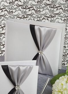 Nostalgia Wedding Memory Book covered in white or ivory satin.  It is decorated with a double layered satin band with a gather in the center.  You can choose the color of both satin bands and you can choose the style of decoration over the gather.