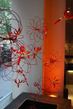 Flowers of the world - Our latest window is an abstract and futuristic design featuring spherical shapes made of red wire accented by hanging red and yellow Gloriosas. Represnting the electricty of summer, the spheres dance in the light while the Gloriosas are a feminine and vibrant touch.