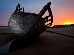 Dilapidated boat in sunset