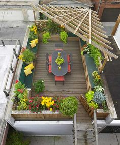 A wooden suspension pergola for privacy and protection from the sun, raised beds for plants and seating make this an inviting rooftop garden.