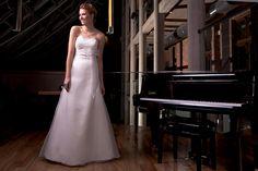 Długa, klasyczna suknia ślubna zdobiona kokardą.