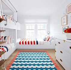 Red, white and blue boys' bedroom features built-in shiplap bunk beds dressed in red, white and blue bedding accented with a white rope ladder as well as a third bed forming an L shape.