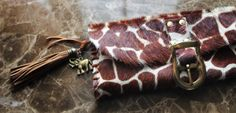 SAVANAH MINI LARGE CLUTCH PURSE FROM OUR WILD IDEAS COLLECTION.  Finished in striking soft, supple, Giraffe imprint on cow hide. Hand laced leather and brass rivets, hardware is antique brass buckle with antique brass magnetic closure.  Each piece in our Wild Ideas collection is a completely original one-off piece of wearable art. No two bags will ever be the same, making you the owner of something truly unique.  Approximate dimensions are: 10x 4 1/2  To browse our full range of bags an...