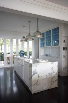 Kitchen with marble, farmhouse sink, tinted glass doors, shiny tiled backsplash and large pendant lamps. Love the folding doors, too.