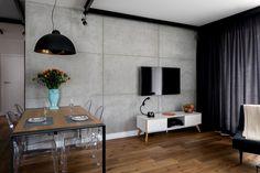 Przewodnim tematem w mieszkaniu na warszawskim Bemowie jest połączenie betonu i stali. Oba te, zimne w odbiorze, materiały skontrastowane zostały płaszczyznami dębowego drewna i oraz meblami i dodatkami o nowoczesnym designie.