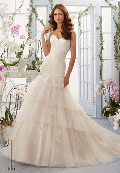 """Wedding Gowns By Blu featuring Soft Net Overlays Alencon Lace Appliques onto the Tiered Gown Available in Three Lengths: 55"""", 58"""", 61"""". Colors available:White, Ivory, Ivory/Cameo."""