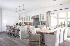 Stunning kitchen features  white shaker cabinets paired with white marble countertops and a linear ...