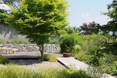 Referenzen Gartengestaltung: Privatgarten. Holz und Steine umhüllt von üppigem Grün.