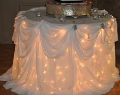 lights under the table linens for your wedding cake table…really like this idea and the draping of the cloth!