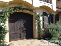 Dark stained garage doors in a French European Style with decorative iron ring pulls and dummy hinges. Call for pricing (714) 900-3667 by DynamicGarageDoors