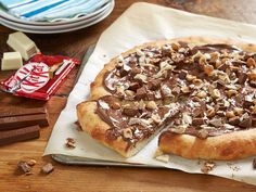 KIT. KAT. PIZZA.   INGREDIENTS  1 lb homemade or store-bought pizza dough  2 tbsp butter, melted  1/4 cup chocolate-hazelnut spread  1 KIT KAT, chopped  1/3 KIT KAT Chunky White, chopped  2 tbsp toasted hazelnuts, chopped   INSTRUCTIONS  Line large baking sheet with parchment and preheat oven to 450°F. Roll the dough on floured surface to create a 9-inch diameter circle and transfer dough to the prepared sheet. Make indentations all over dough with fingertips and brush melted butter over…