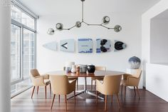 In the dining area, a chandelier by Lindsey Adelman Studio is suspended over a Florence Knoll table and Osvaldo Borsani chairs, near a surfboard sculpture in polystyren...