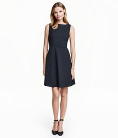 Sleeveless dress in woven, slightly stretchy cotton-blend fabric. Fitted bodice with boat neck, seam at waist, and circle skirt. Decorative seams at top and concealed zip at back. Lined.