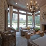 The well-lit sunroom of this sophisticated, elegant Tuxedo Park mansion in Atlanta includes a fireplace for added warmth and ambiance. See more of the home at FrontDoor.com. | HGTV FrontDoor
