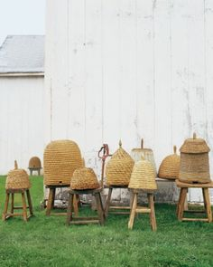 Dome-shaped bee skeps made of coiled or braided straw were commonly used on farms as beehives until modern methods were developed in the mid-19th century. This lovely collection is displayed on rustic stools. Lovely!