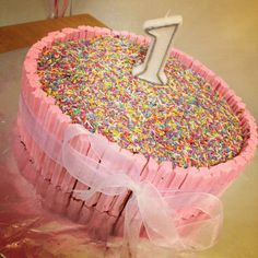 Chocolate mudcake surrounded by musk sticks and covered in rainbow sprinkles - very easy!