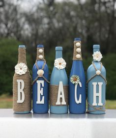 Recycled wine bottles crafted with paint, twine, and letters to spell BEACH Can make in other colors Liquor Bottle Crafts, Recycled Wine Bottles, Wine Bottle Art, Painted Wine Bottles, Diy Bottle, Liquor Bottles, Bottles And Jars, Glass Bottles, Wine Bottle Lighting