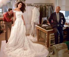 Alamuddin at a final fitting, with Oscar de la Renta (right) and  head tailor Raffaele Ilardo, in the designer's New York studio. Oscar de la Renta ivory beaded-tulle dress with Chantilly-lace appliqué.