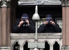Police spotters watch as crowds gather to watch the funeral procession of Margaret Thatcher's coffin