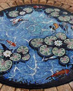 The Carterton Lily Pond Mosaic designed by Gary Drostle. Exterior floor mosaic koi pond in Carterton, Oxfordshire, United Kingdom. Pebble Mosaic, Mosaic Art, Mosaic Glass, Mosaic Tiles, Stained Glass, Glass Art, Rock Mosaic, Mosaic Floors, Flooring Tiles