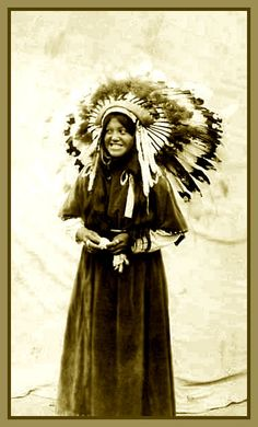 Yakima woman known as Sunbeam in feathered headdress, Washington. Photograph: ca. 1913. And what a great smile.