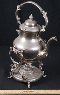 VINTAGE SILVER ON COPPER ROCKING TEA OR COFFEE POT ON BASE. THIS LOVELY PIECE HAS AN ORNATE FLORAL AND SCROLL DESIGN. THE BASE OPENS UP SO AS TO ADD A FLAME AND KEEP THE CONTENTS INSIDE WARM. IT BEARS THE HALLMARK OF THE MAKER ON THE BOTTOM OF THE POT. MEASURES 14 INCHES TALL.