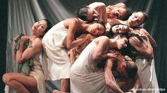 Pina Bausch's Dance Company. Mehrer Tänzer in weißen Hemden und Kleidern winden sich ineinander. (c) dpa