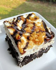Snickers Cake 1 box devils food cake mix, plus ingredients to make the cake 1 can sweetened condensed milk 1 jar Smuckers hot caramel ice cream topping 1/2 cup chocolate chips 2 cups heavy whipping cream 1/2 cup powdered sugar 1 tsp vanilla 3 snickers candy bars, chopped 1/3 cup peanuts, chopped caramel sauce chocolate sauce Bake