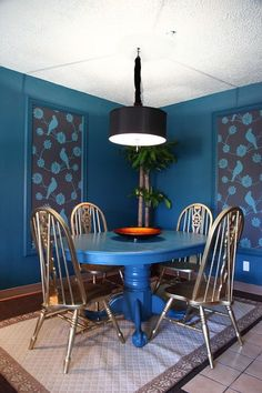 This page has some excellent design ideas on a budget. Like this one here: A basic table & chairs become instantly more interesting with unexpected spray paint colors. Then add some thrift store frames with cuts of wall paper of found fabric. Beautiful.