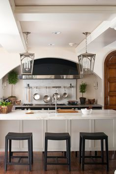 Large-scale nickel lanterns over the kitchen island not only provide light and scale, but continue the clean lines and stainless-steel theme of nearby appliances - Traditional Home®
