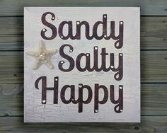 Beach decor. Sandy Salty Happy coastal beach sign. Rustic wooden plaque painted brown base with a crackle texture off-white top coat. Letters are made from hand painted watercolor paper in shades of dark brown. During checkout, you can choose rhinestones accent on the words Sandy Salty Happy. A knobby starfish with a rhinestone complete this beachy wooden plaque. There is a saw tooth hanger on the back if you want to hang it on your wall. It can also adorn your mantle, dresser, or entry…
