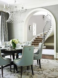 Amy Bergman Traditional Home Mag Gorgeous dining room design with gray grasscloth wallpaper, white wire chandelier, arched doorway, glossy black round dining table, white Tissage Chandelier, Urban Electric Co. Olga Sconces, baker turquoise blue tufted chairs with nailhead trim, gray & blue circles window panels curtains and vine rug. Ralph Lauren Cymric Silver