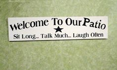 Welcome house patio sign for outdoor on wood. Hand painted, it says; Welcome to our Patio, Sit Long, Talk Much, Laugh Often. Measures approx 24 in
