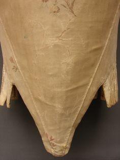 1751-1775 - France - Corps à baleines fermé devant en taffetas écru liseré, broché de fils de soie écrus et polychromes, avec des ramages en brindilles et des petits motifs placés de bouquets. Le dos et le devant sont doublés d'une toile de lin écrue. La forme du corps et les étoffes employées indiquent une datation vers 1750-1775.