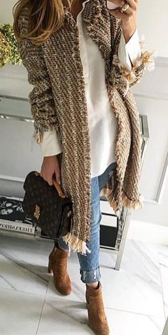 Woven beige cardigan over white shirt and blue jeans.