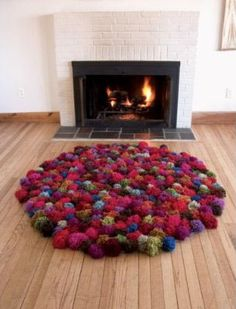 Make about 225 yarn pompoms that are the same size.  Use burlap, an old t-shirt, or anti-slip rug canvas as the base for the rug .Attach the pompoms to the rug base.