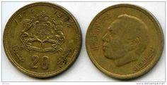 """Dirham marroquino (1960-em uso) (x) 20 santimat (1974) O: efígie do rei Hassam II (1929-1999, rei de Marrocos entre 1961 e 1999) e em árabe """"reino do Marrocos""""/R: brasão de armas marroquino (composto por um pentagrama perante a representação das Cordilheiras do Atlas, um Sol nascente e uma coroa real, dois leões segurando o escudo e abaixo a inscrição do alcorão em árabe """"Se acudires a Deus, ele acudir-te-á"""", valor e em árabe """"reino do Marrocos"""") e o ano no calendário islâmico."""