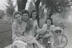 Four participants (Mary Lou Ciulla, Annie Gambino, Bessie Parisi, and Vita Valenza) of a bike hosteling trip sponsored by Neighborhood House, resting on a low wall and smiling for the camera. 1940s