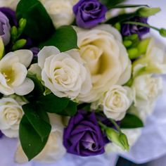 Bridesmaid bouquet of Avalanche and spray roses with purple lisianthus and freesia by Apple Blossom Flowers #whiteandpurpleflowers
