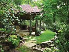 A wooded area surrounds a private outdoor kitchen. A stone walkway and floor contribute to the rustic charm of this outdoor room.