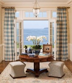 Centered round table topped with blue and white porcelain, orchids and buffalo check curtains flanking french doors with ocean views - North Shore home by Windham House