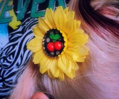 Yellow Daisy with Cherry Hair Clip by Sins 'n Needles - This pretty little hair flower is bright yellow, features a recycled bottle cap center with cherry, comes in your choice and white with black dots or black with white dots, and is securely fastened to a silver tone alligator clasp. Measures approximately 3 inches across.