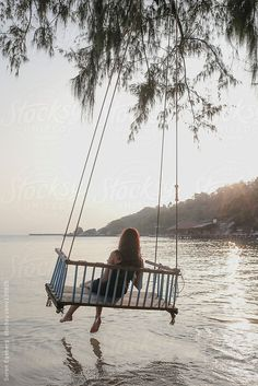 Young girl using tablet computer in seated rope swing over the ocean water on tropical island by Soren Egeberg