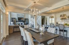 This white contemporary dining room has an elegant coffered ceiling and plush dining chairs that are paired with a rustic hardwood dining table for a rustic-chic look. The open floor plan of the dining room flows into the kitchen and living room.