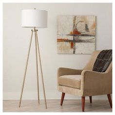 Standing delicately yet strong on 3 slender legs, the Threshold Ellis Metal Floor Lamp brings incandescent style to your living room or bedroom. The base built from slim brass posts connects to shining hardware for a graceful, modern furniture look all capped off with a simple white shade. This look pairs with a wide variety of furniture styles for a versatile lighting option you'll love.