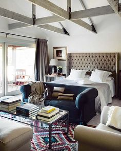 i love how this has the vibe of a lived-in hotel room: big bed, table and chairs, but a funky rug and books.... and love that ceiling - love exposed beams