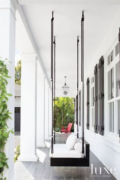 luxe-interiors-and-design:  14 Stylish Lounge and Seating Spots On this front porch, an ebonized oak swing built by D & A Studio hangs near a charred iron lantern from Farrey's.