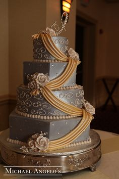 Gold & Gray #9Drapery  This four tier hexagon and round cake is iced in a gray buttercream. It is then trimmed with ivory boarders and swirls then accented with gems. The golden luster fondant drapes are then accented with ivory gum paste roses. The topper was brought in.