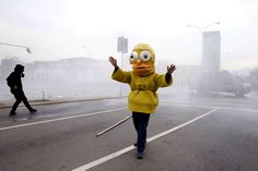 A protester dressed as Homer Simpson steps between demonstrators and police in an attempt to stop cl... - Luis Hidalgo/AP